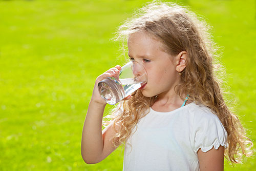 Girl drinking water outside