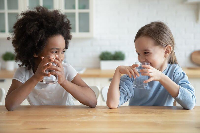 2 girls drinking water in a kitchen